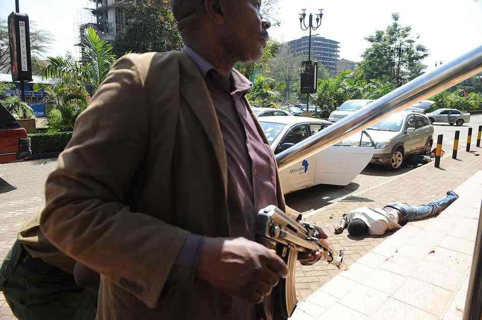 The body of a man lies on the ground as plainclothes policemen try to gain entry into the Westgate mall on Saturday. Ten to 15 attackers remain in the mall and Kenyan forces control the security cameras inside the shopping cent