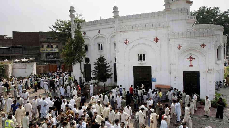 People gather outside All Saints Church in Peshawar, Pakistan, Sunday, after a suicide bombing attack killed scores o
