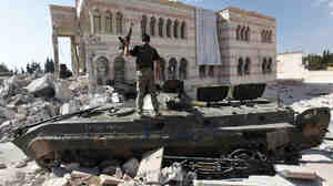 A Free Syrian Army soldier stands on a Syrian military tank in front of a damaged mosque in the Syrian town of Azaz in September 2012. A different rebel group, an al-Qaida offshoot, took over the town on Wednesday.