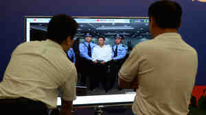 Men watch a TV screen showing former Chinese politician Bo Xilai, who was sentenced to life in prison Sunday by a court in Jinan, Shandong Province.