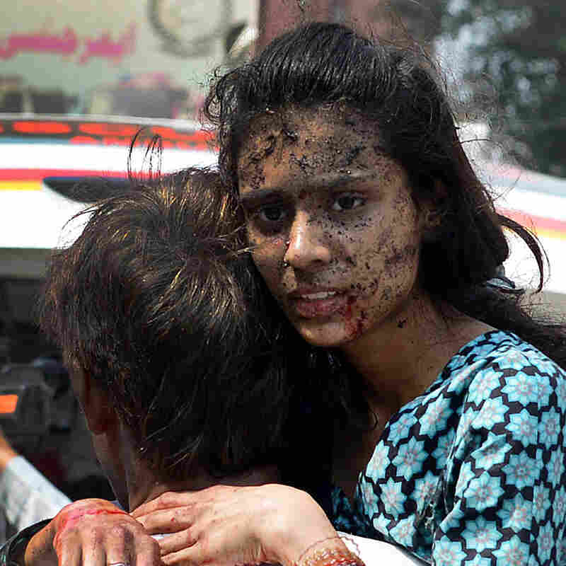 A woman is carried into the hospital after being injured when two suicide bombers attacked a church in Peshawar, Pakistan, on Sunday.