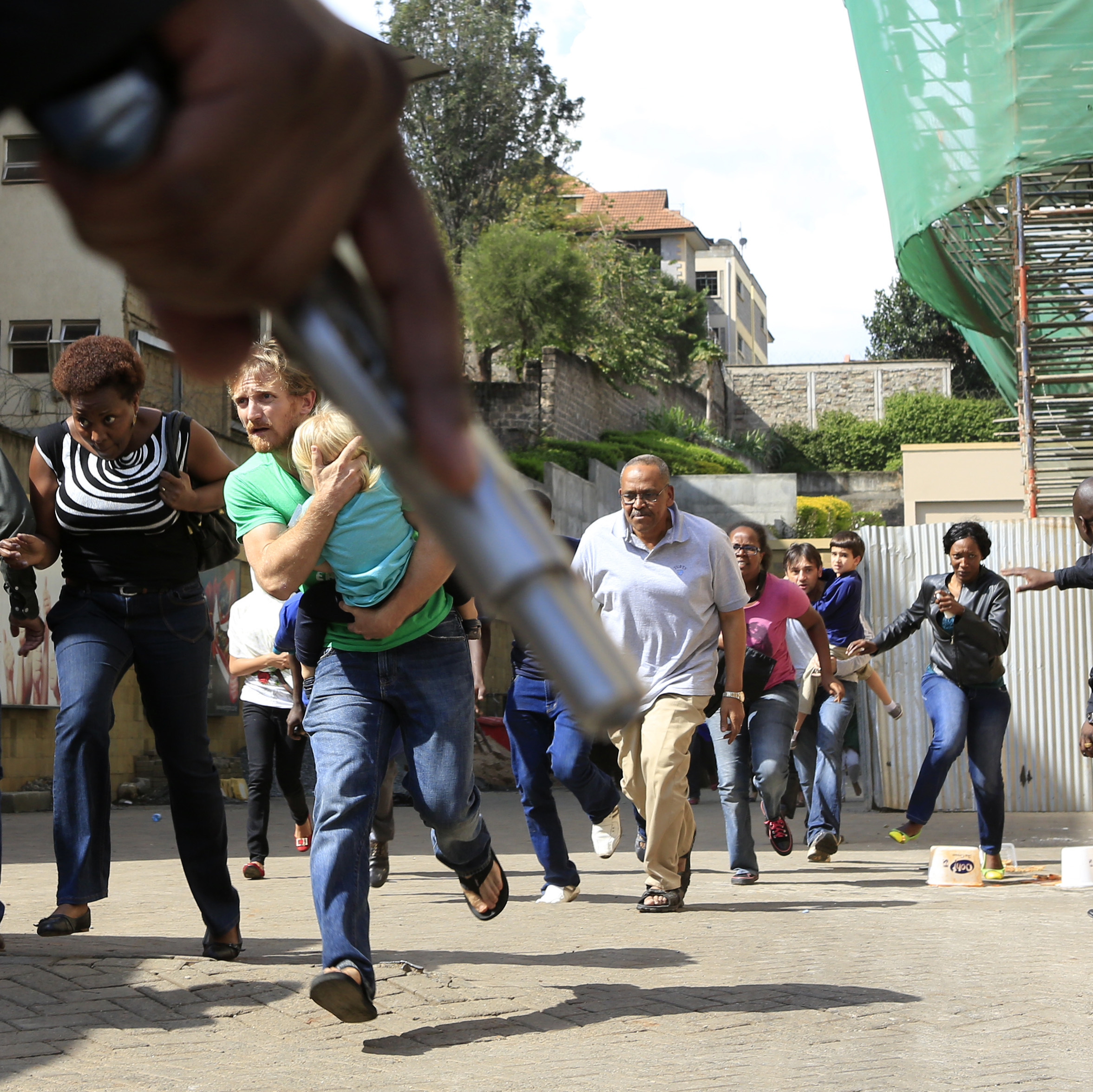 A police officer's hand, holding a gun, as security personnel pointed people to safety Saturday at the Westgate Mall in Nairobi. Among those in the photo is a friend of Associated Press correspondent Jason Straziuso. It's the man who is clutching his daughter as they run by.