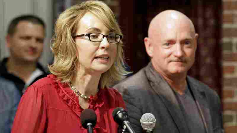 Former Arizona Rep. Gabrielle Giffords, accompanied by her husband, retired astronaut Mark Kelly, speaks during a news conference in Manchester, N.H., in July. They were there to encourage state political leaders to have courage in the fight to expand background checks on gun purchases.