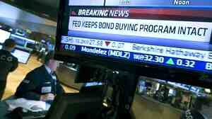 A television monitor on the floor of the New York Stock Exchange shows the decision the Federal Reserve made on Sept. 18, 2013.