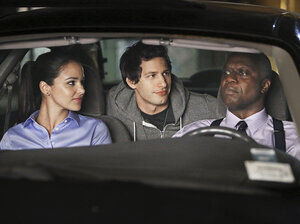 Capt. Ray Holt (Andre Braugher, right) leads detectives Jake Peralta (Andy Samberg) and Amy Santiago (Melissa Fumero) on a police stakeout in Brooklyn Nine-Nine.