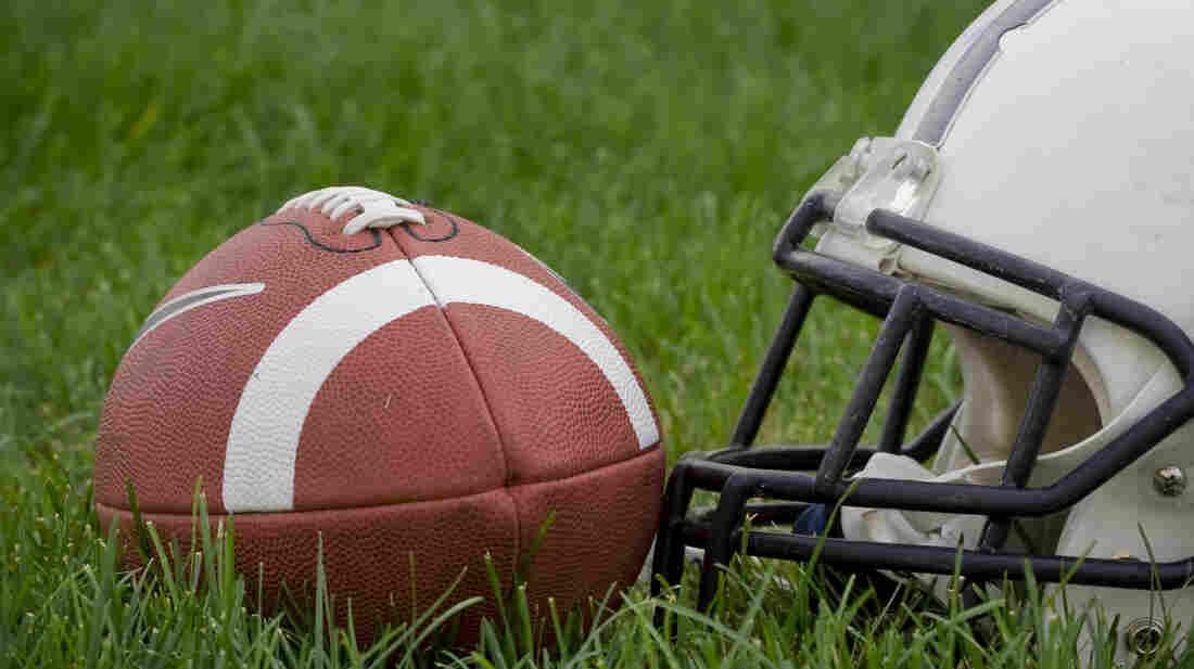 An American football and a helmet on a grass field