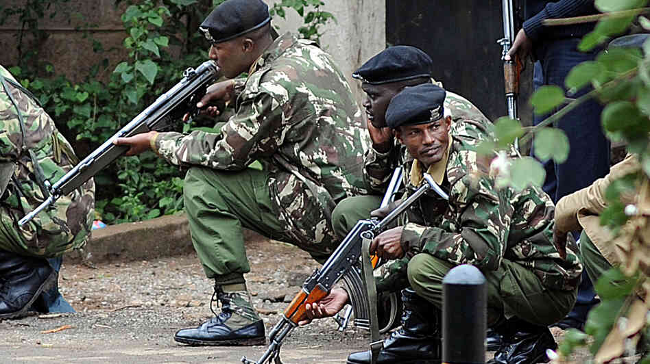 Kenyan police officers take cover outside the Westgate mall in Nairobi on Monday.