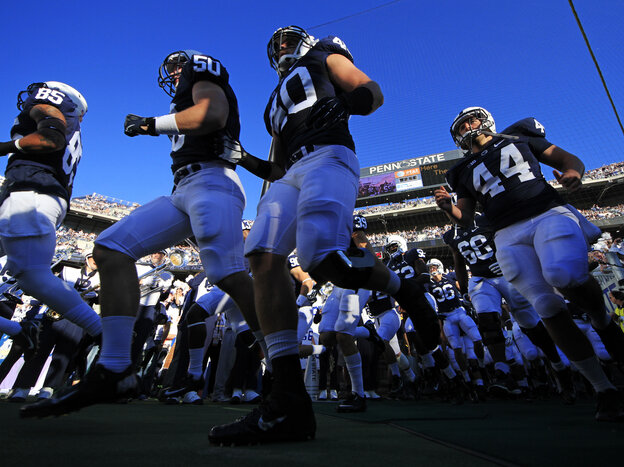 Penn State football players run onto the field earlier this month in State College, Pa.