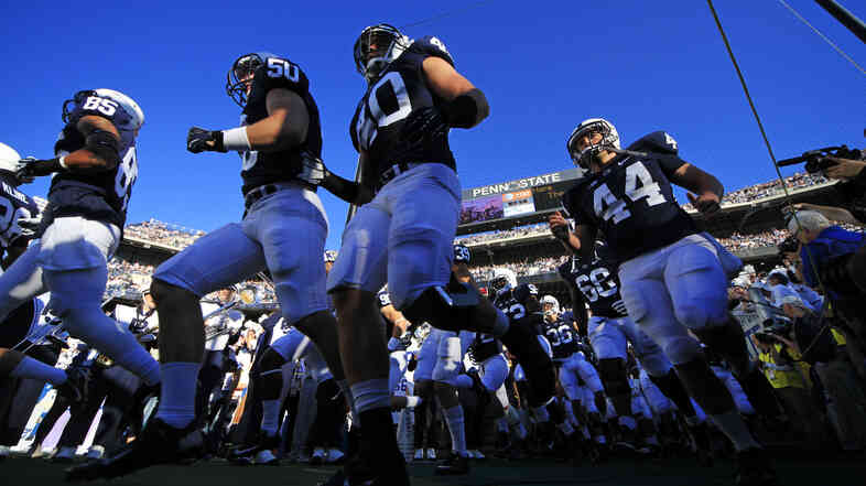 Penn State football players run onto the field earlier this month in State