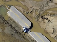 An abandoned car lies off a road devastated by floodwaters along the South Platte River east of Greeley, Colo., on Sept. 17.