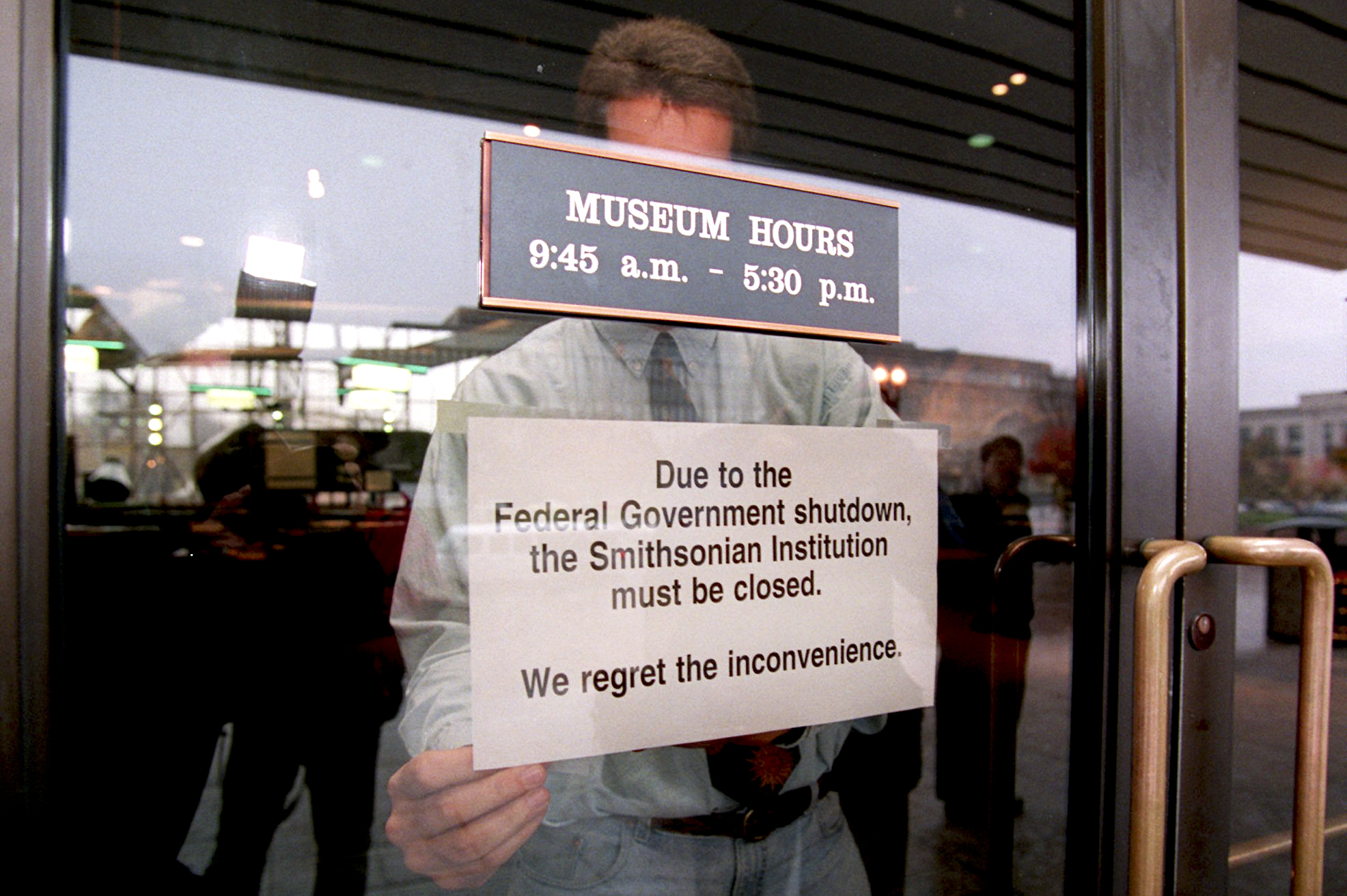 Mike Fetters attaches a sign to a door of the Smithsonian's Air and Space Museum in Washington on Nov. 14.