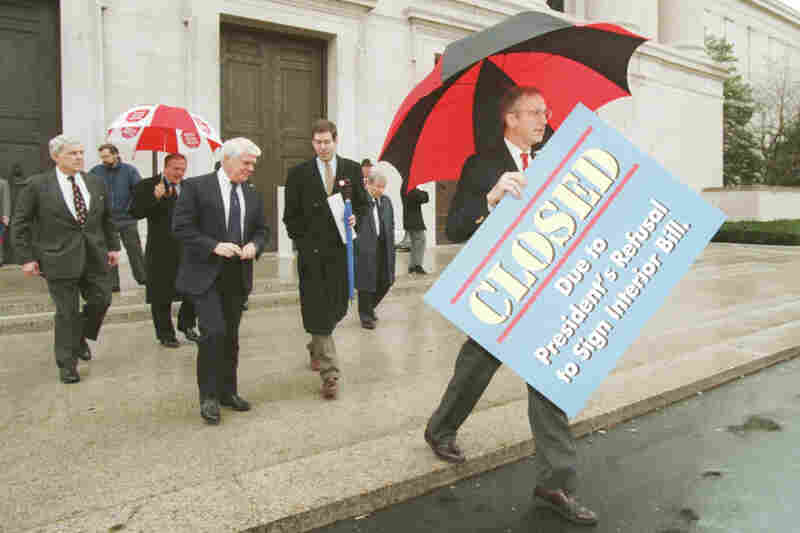 "House Appropriations Committee Chairman Bob Livingston, R-La., holds a ""closed"" sign outside the National Gallery of Art on Dec. 18 as another partial shutdown of the federal government began. Joining Livingston were Rep. Ralph Regula (left), R-Ohio; Rep. Sherwood Boehlert, R-N.Y.; Rep. Jerry Lewis, R-Calif.; and Lewis' press aide Dave LesStrang."