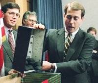 Rep. John Boehner, R-Ohio, dumps out coal, which he called a Christmas gift to President Clinton, during a Dec. 21 Capitol Hill news conference. The White House and congressional Republicans labored to restart balanced budget talks.