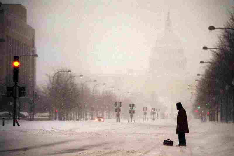 With the Capitol in the background, a lone pedestrian waits for a ride on Pennsylvania Avenue as snow falls on Jan. 8. That winter storm paralyzed the city and closed the federal government, just two days after it reopened.