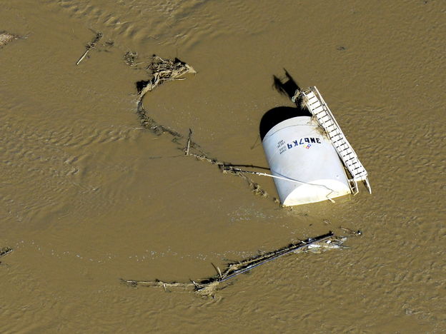 A crude oil storage tank lies on its side in floodwaters along the South Platte River, in Weld County, Colo., on Sept. 17. Hundreds of natural gas and oil wells along with pipelines are shut down by flooding, as state and federal inspectors gauge the damage and look for potential contamination from inundated oil fields.