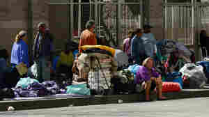 "Homeless people rest on a public sidewalk early this year in downtown skid row area of Los Angeles. The United Way of Greater Los Angeles is attempting to end ""chronic homelessness"" by 2016 with a model that identifies the neediest cases and provides them with permanent homes."