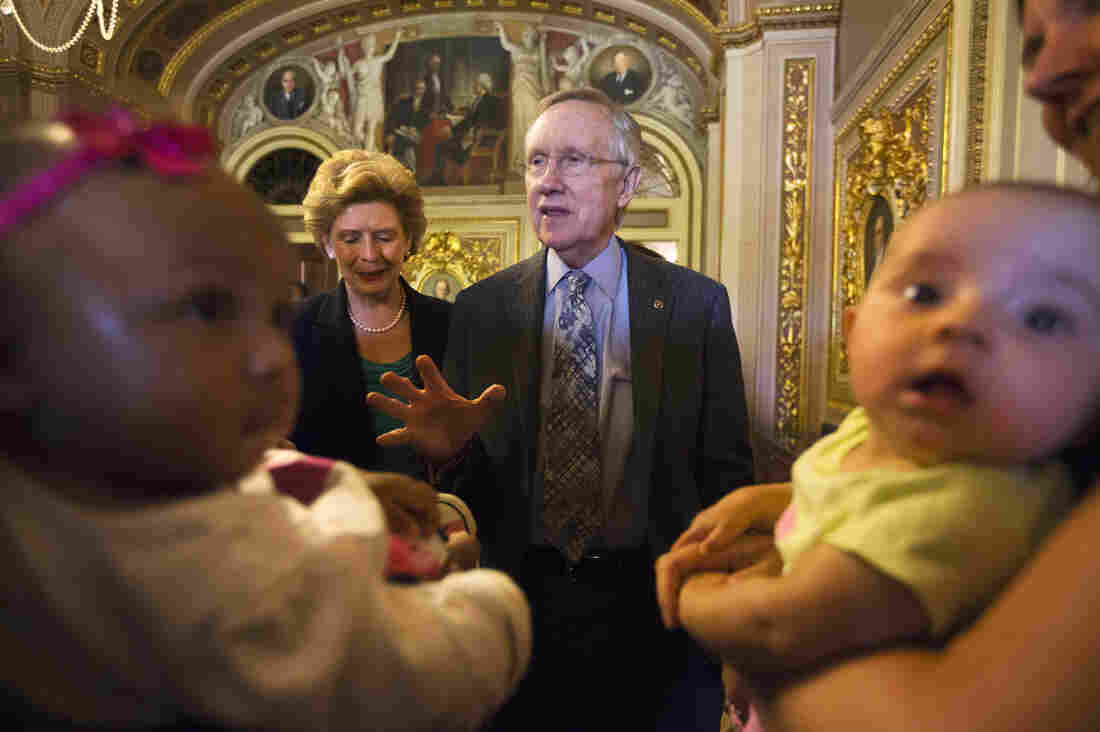Democratic Sens. Harry Reid of Nevada and Debbie Stabenow of Michigan visited with mothers and babies at a Capitol Hill Obamacare event Wednesday.