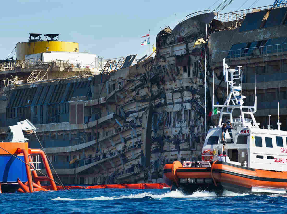 A Coast Guard patrols in front of the severely damaged right side of the Costa Concordia cruise ship after it was righted last week.