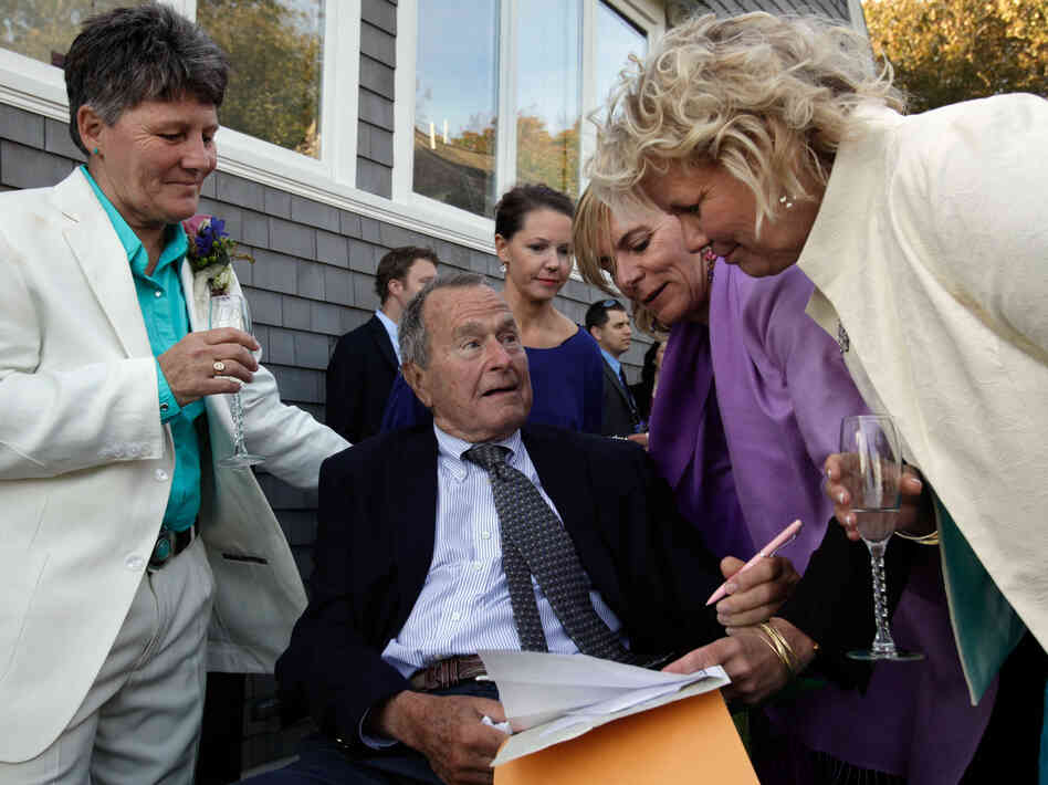 Former President George H.W. Bush prepares to sign the marriage license of friends Helen Thorgalsen, right, and Bonnie Clement, left, in Kennebunkport, Maine, as officiant Nancy Sosa, third right, a