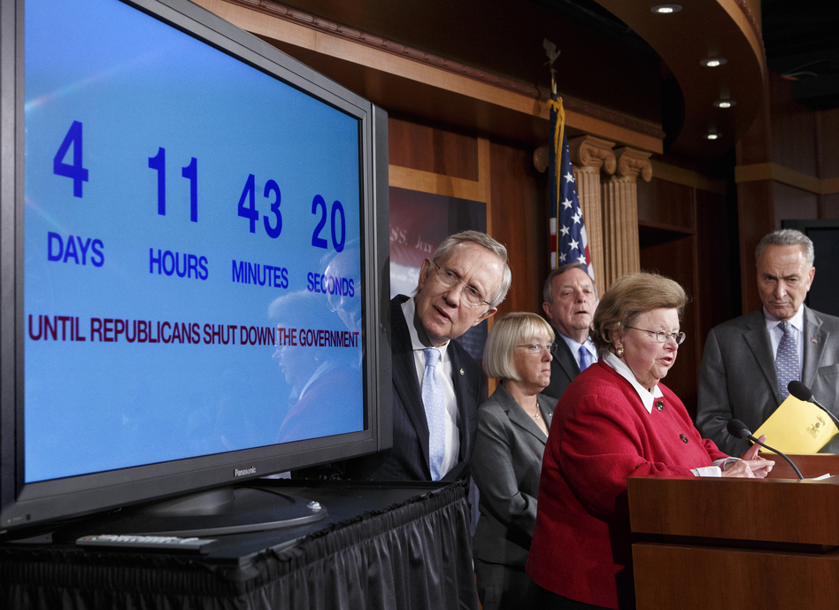 Senate Majority Leader Harry Reid, D-Nev., looks at a countdown-to-shutdown clock during a news conference in the Capitol on Thursday. (J. Scott Applewhite/AP)