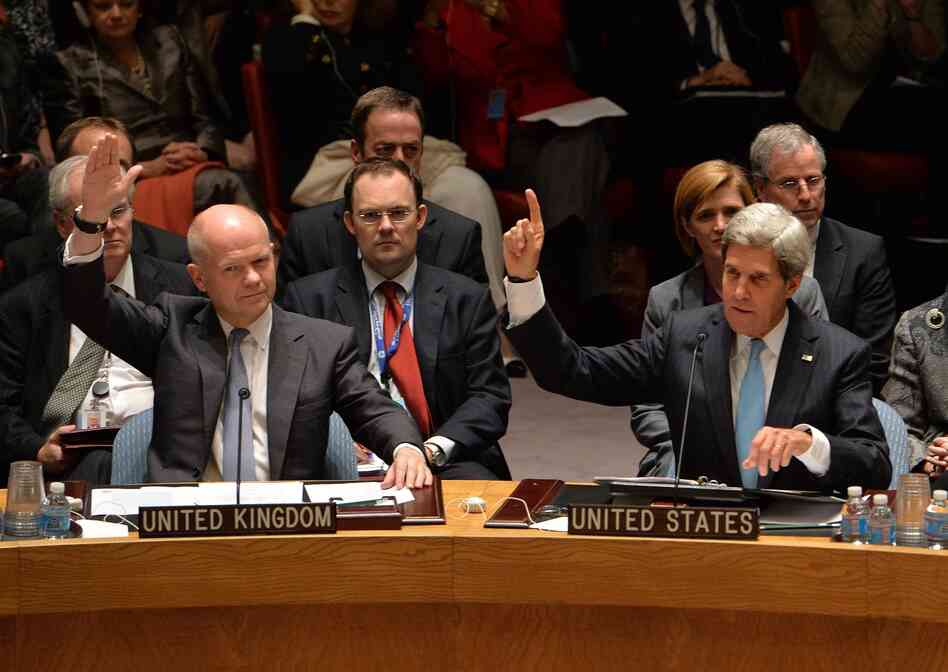 Britain's Foreign Minister William Hague, left, and US Secretary of State John Kerry, right, vote to approve a resolution that will require Syria to give up its chemical weapons during a meeting on Friday at U.N. headquarters in New York.