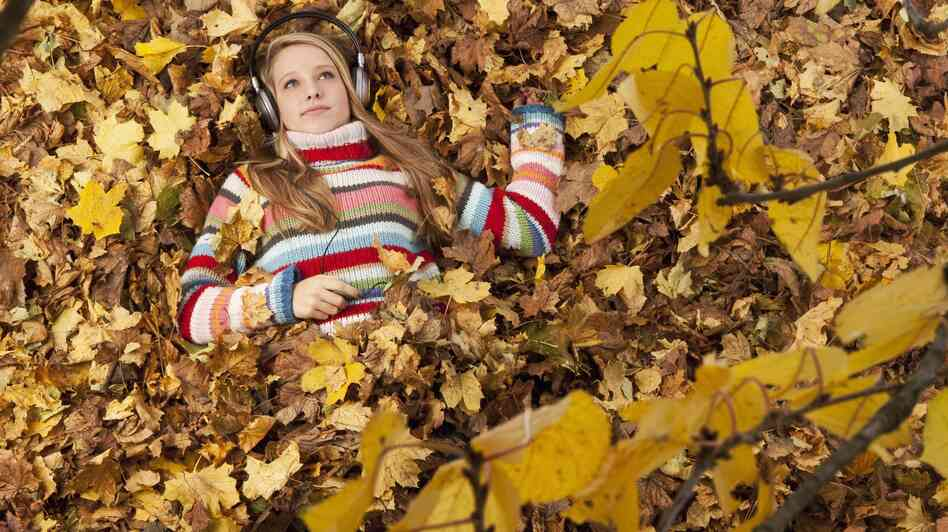Woman lying in leaves, listening to music.