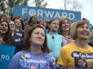 Supporters look on as President Obama speaks about the choice facing women in the upcoming election at an October 2012 campaign event.