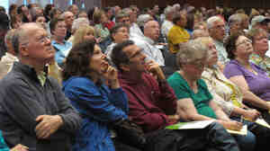 The audience concentrates on a presentation by Kansas Insurance Commissioner Sandy Praeger's office about the federal health care ov