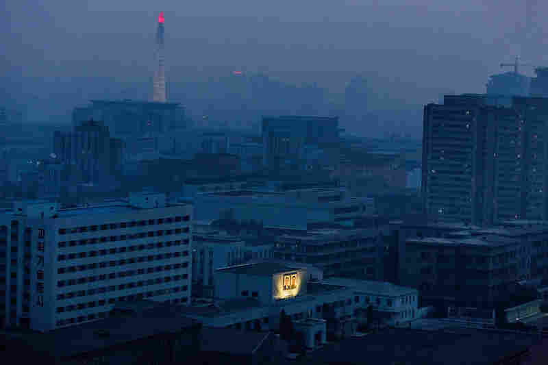Portraits of Kim Il Sung and his son, Kim Jong Il, are still lit up in Pyongyang at dawn. Even during the city's blackouts, electricity is reserved to light the flame atop Juche Tower in the distance.