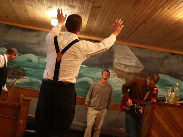 Jacob Grey raises his hands in Pastor Andrew's church.