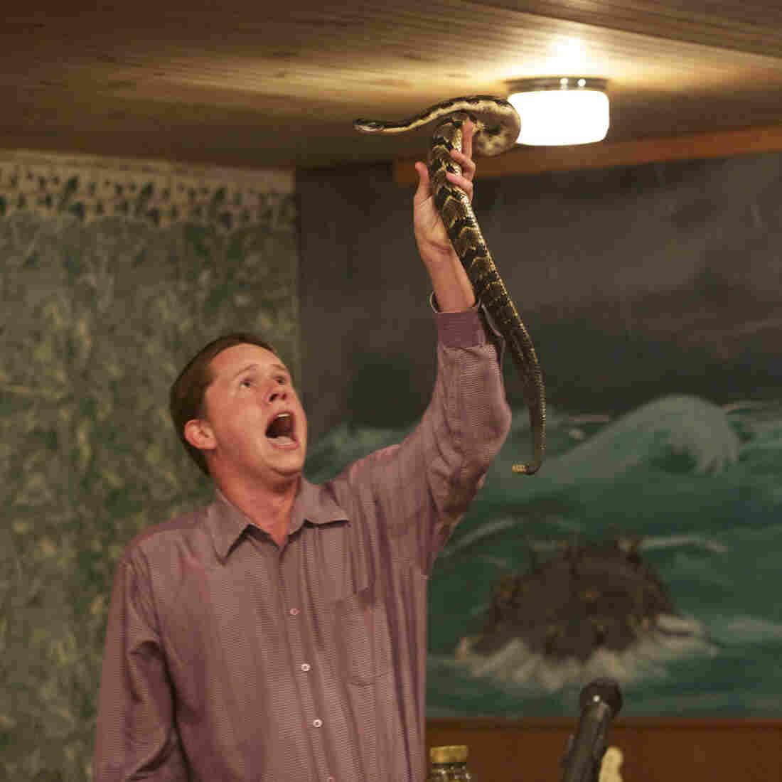Andrew Hamblin preaches while holding a snake above his head, LaFollette, Tenn.
