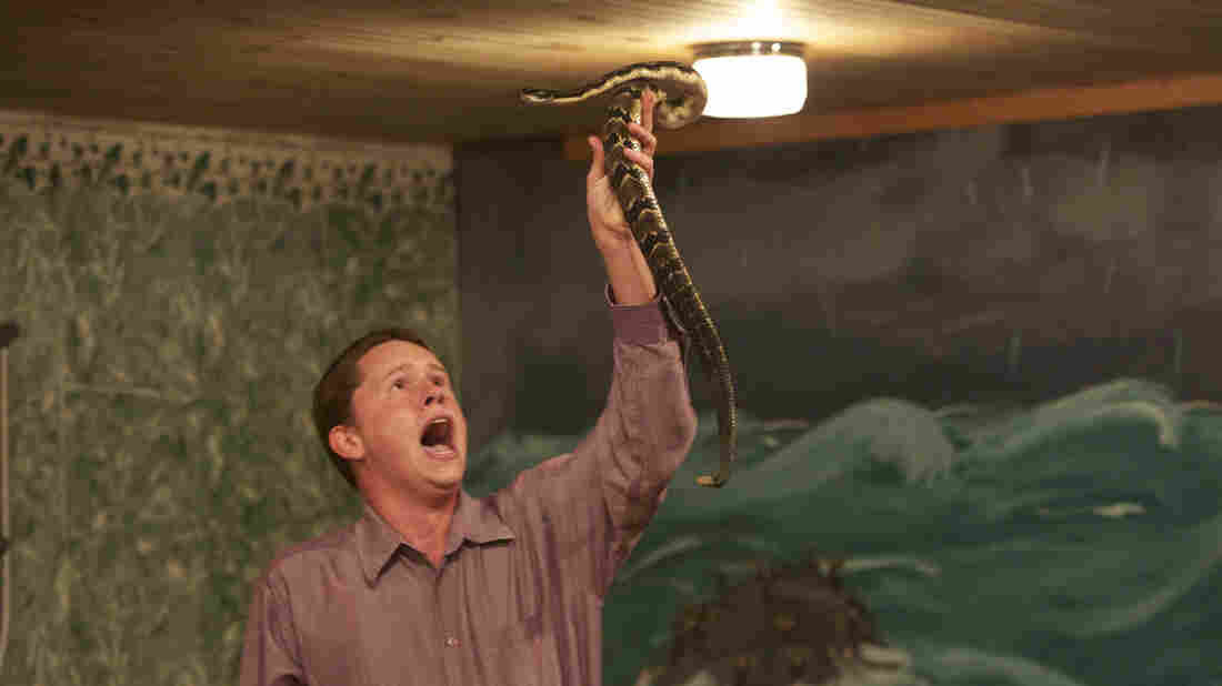 Andrew Hamblin preaches while holding a snake above his head, LaFollette, Tenn.