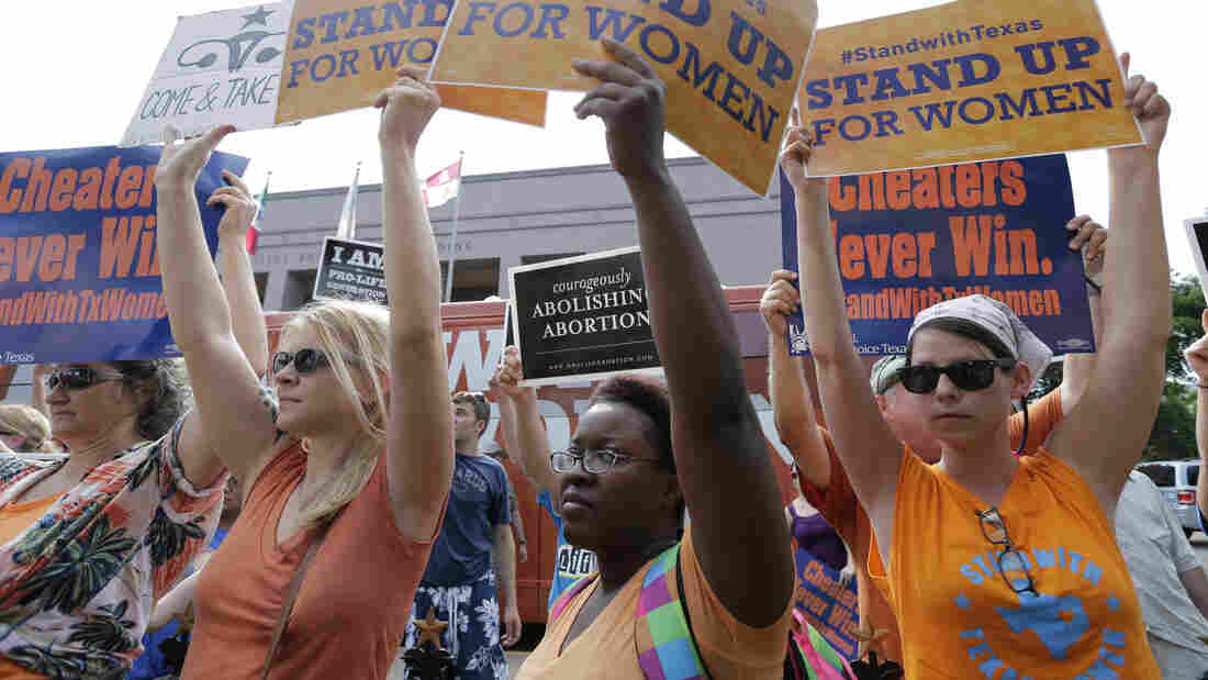 Women's health clinics have sued the state of Texas over its new abortion law, which they say will close more than a third of abortion providers in the state. Here, advocates for and against the bill are seen outside the Texas Capitol in Austin in July.