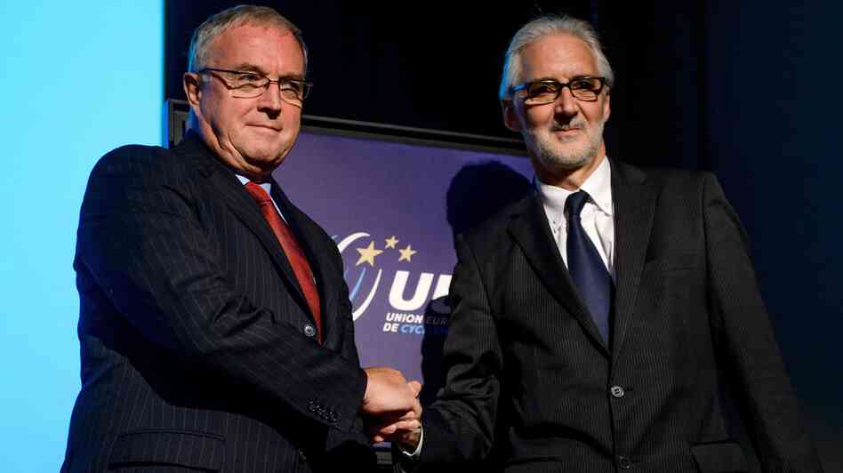 The incoming president of the International Cycling Union, Brian Cookson (right), shakes hands earlie