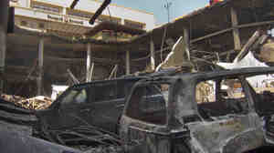 The upper parking lot entrance to the Westgate Mall is seen above vehicles that plunged during the collapse of the upper level. Kenyan officials are urging patience with the pace of the flow of information about the attack.