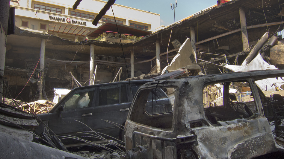 The upper parking lot entrance to the Westgate Mall is seen above vehicles that plunged during the collapse of the upper level. Kenyan officials are urging patience with the pace of the flow of information about the attack. (AP)