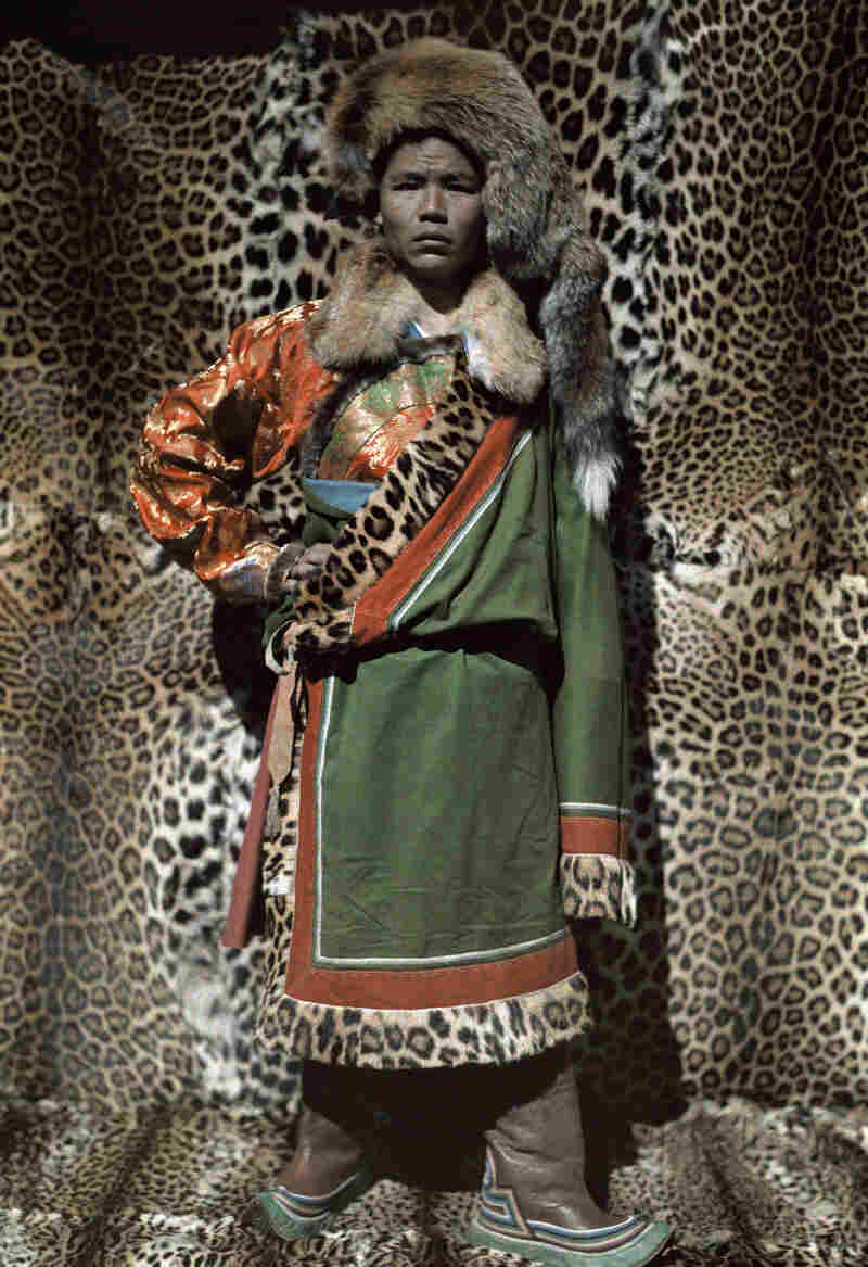 Tibet, China. A Nashi man stands in front of robes made from leopard skin. 1931