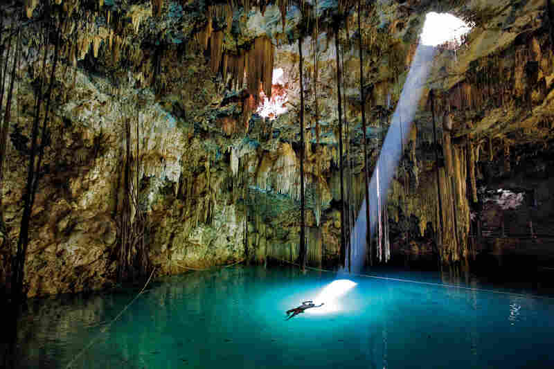 Stalactites and a sunbeam spotlight a swimmer in the Xkeken cenote, a natural well in the Yucatán thought by the Mayans to lead to the underworld. Dzitnup, Mexico, 2010