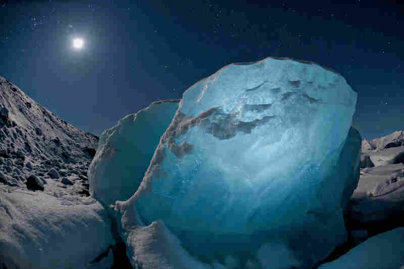 Destined to melt, an 800-pound chunk of ice glowed in the moonlight. It washed up in a lagoon created by a receding glacier, part of a worldwide shrinkage of glacial ice. Jokulsarton, Iceland, 2009