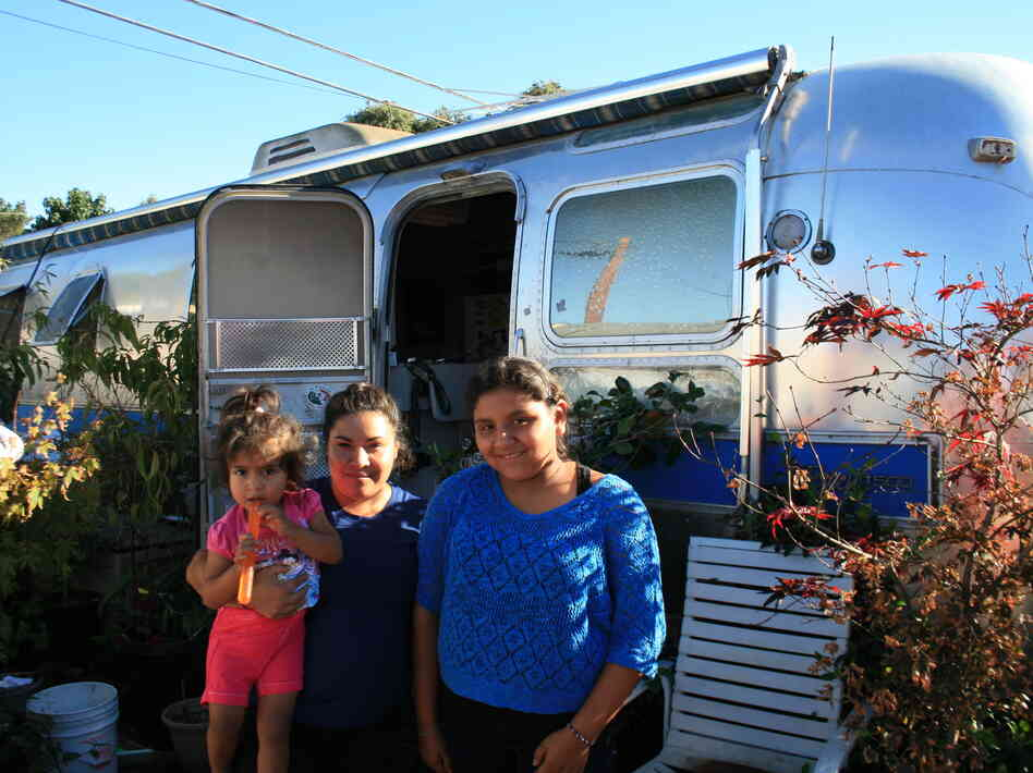 Palo Alto middle school student Jennifer Munoz Tello (right) stands outside her family's trailer in Palo Alto with her mother, Sandra, and 2-year-old sister, Cynthia.