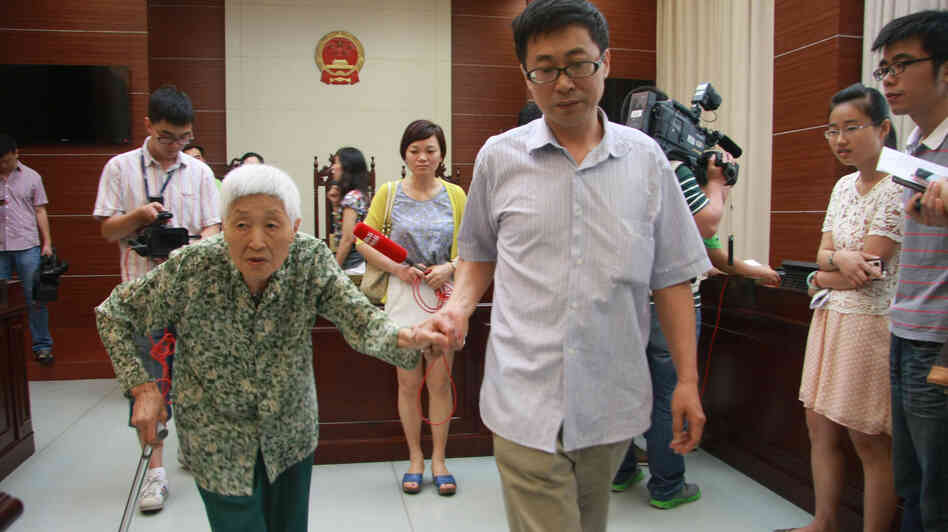 A woman surnamed Chu (left), 77, attends the hearing of a case against her daughter and husband in Wuxi, east China's Jiangsu province, on July 1. Chu's daughter has been ordered to visit her at least once every two months, in the first case under a new law to protect the elderly.