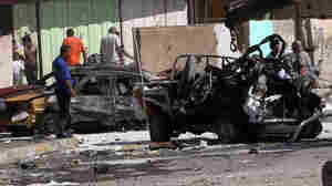 Iraqis look at the site of a car bomb attack in Baghdad, where at least 10 car bombs were detonated during the city's rush hour Monday.