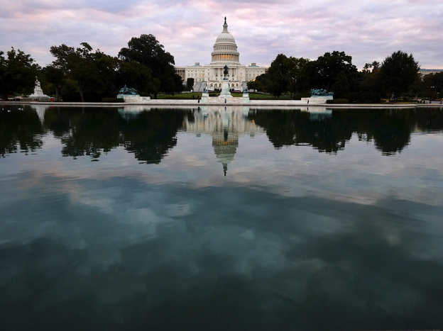 The Capitol is mirrored in its reflecting pool early Tuesday, as the partial federal shutdown began. But there's a battle still to come in which the stakes are even higher.