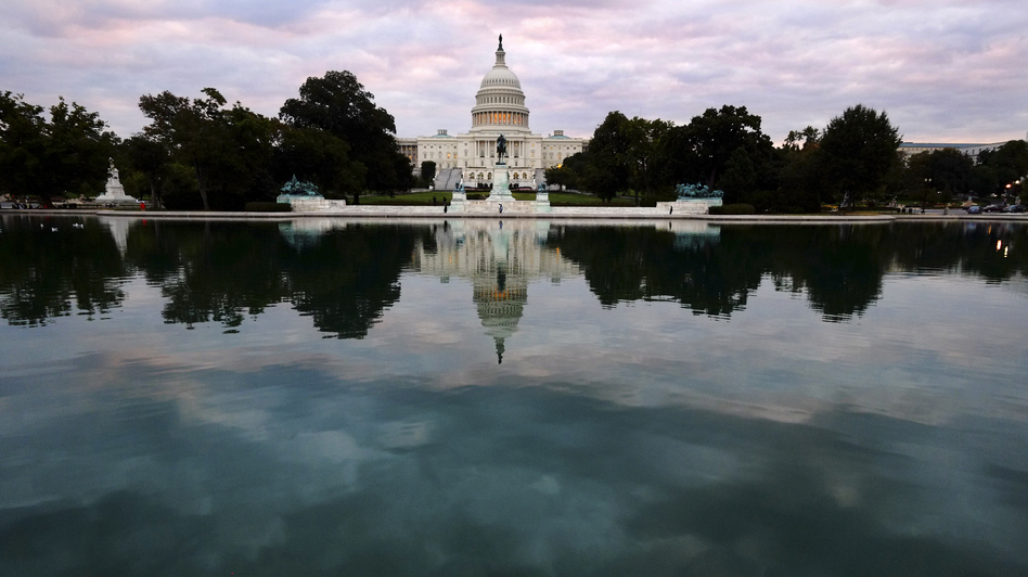 The Capitol is mirrored in its reflecting pool early Tuesday, as the partial federal shutdown began. But there's a battle still to come in which the stakes are even higher. (AP)