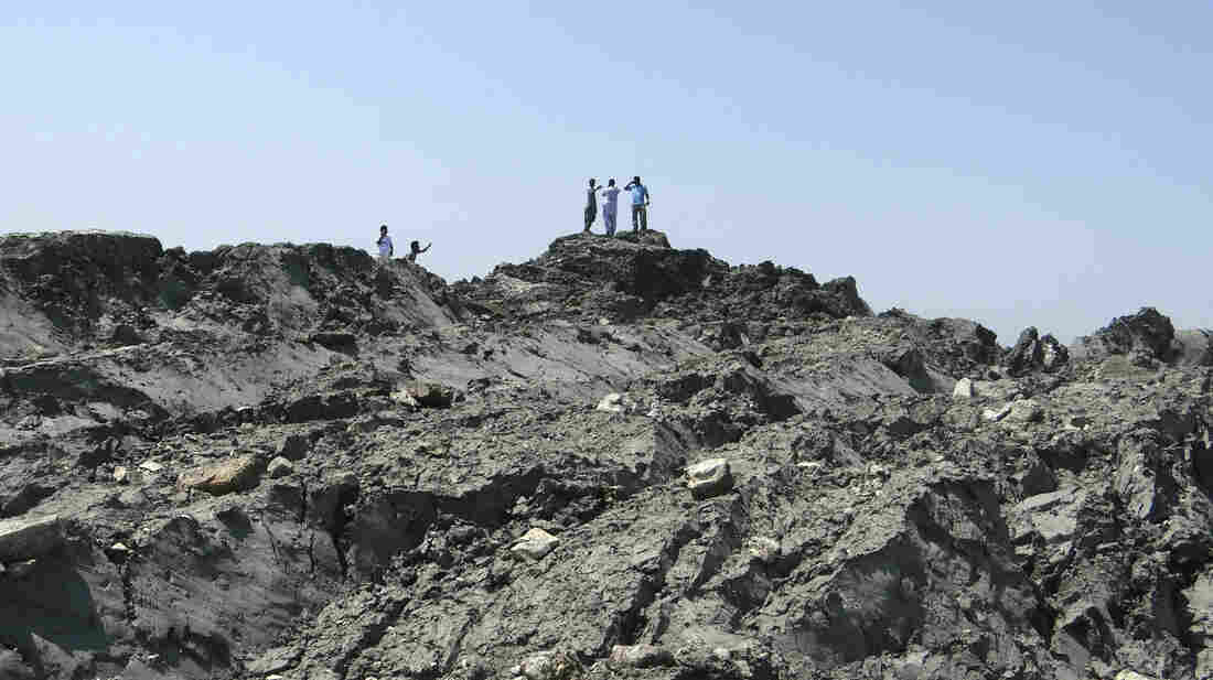 Pakistanis walk on an island that emerged off the coastline of the Arabian Sea following a deadly magnitude 7.7 earthquake in Pakistan's southern province of Baluchistan on Sept. 24.
