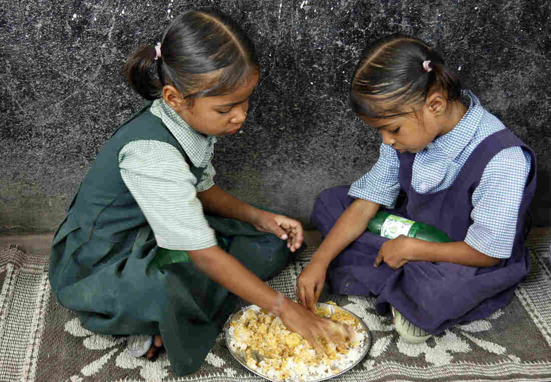Schoolgirls eat a free midday meal in Hyderabad, India, last month. India has offered such meals since the 1960s to persuade impoverished parents to send their children to school. A U.N. report released Tuesday finds modest progress in the worldwide fight against chronic hunger.