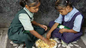 Schoolgirls eat a free midday meal in Hyderabad, India, last month. India has offered such meals since the 1960s to persuade impove