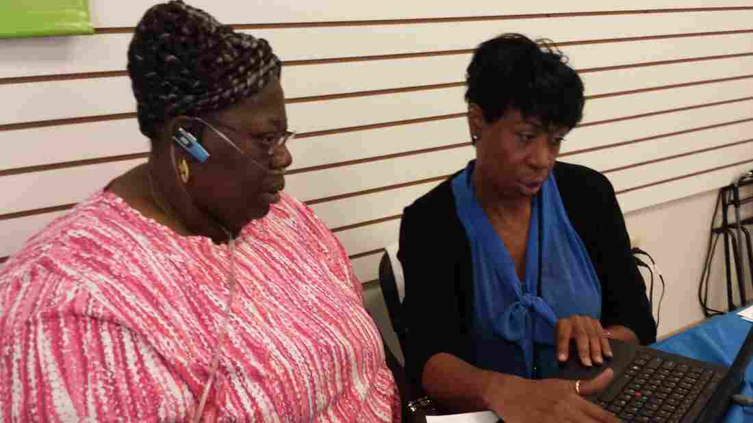 Onita Sanders (right), a certified application counselor at the Southeastern Virginia Health System, helps Virginia resident Brenda Harrell with health coverage options at Enrollfest in Hampton, Va., on Tuesday.