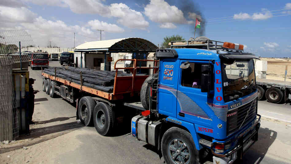 Palestinians inspect trucks loaded with iron arriving from Israel through the Kerem Shalom border crossing into Rafah, southern Gaza Strip, on Sept. 22. The delivery of the materials to the private sector is a first since the Hamas takeover in 2007.