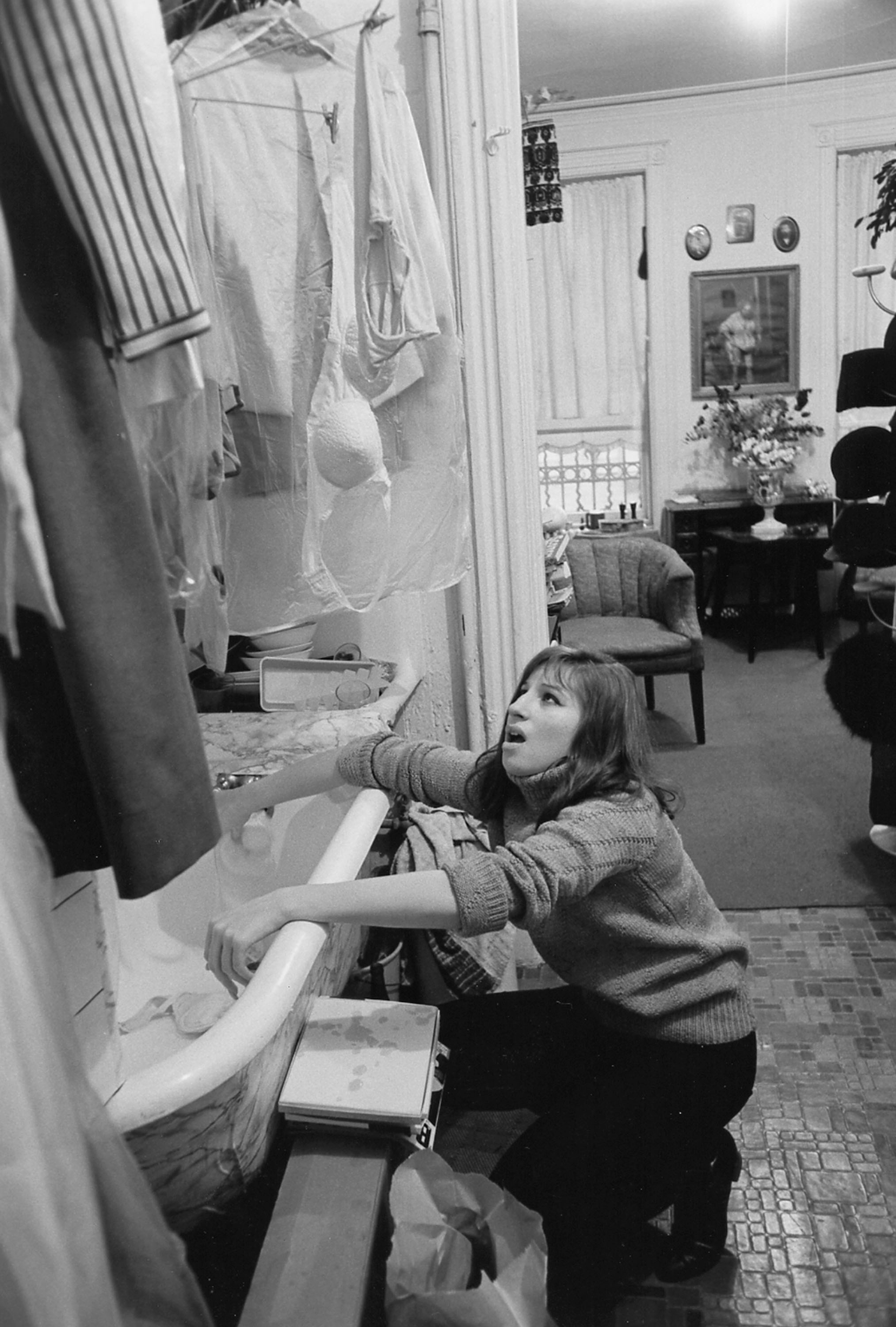 Streisand in the kitchen of her New York City apartment, 1964. The bathtub in the kitchen was standard for that type of apartment.